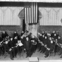 Black and white photograph of Director Arthur Wasshausen leading the Citizens Band in Crookston's opera house in 1907.