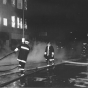 Black and white photograph of firefighters battling the flames in the Opera House Block in 1987.