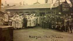 Black and white group photograph taken outside a Red Cross hut by Red Cross worker Julia Gray, 1919.