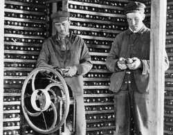 Black and white photograph of Martin Carlsted turning the handle of a manual corn sheller to remove kernels, c.1910.