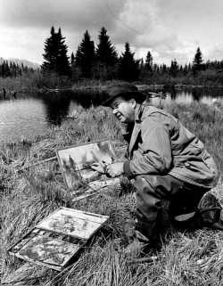 Birney Quick painting a landscape out in nature, along the shore of a lake, with pine trees in the background.