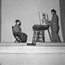 Black and white photograph of Birney Quick painting an image of a young man sitting on a chair in front of him.