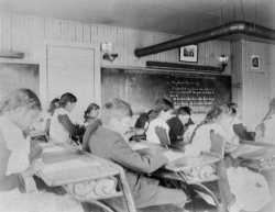 """Black and white photograph of """"intermediate"""" students inside a classroom at an Native American boarding school in Beaulieu, c.1900."""