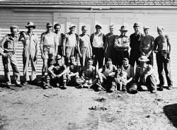 Black and white photograph of German prisoners of war outside a farm building in Moorhead, ca. 1943–1945. Used with the permission of the Historical and Cultural Society of Clay County.