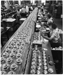 Black and white photograph of Honeywell Round thermostats ready for final checkout and packaging at a factory in Golden Valley, c.1955.