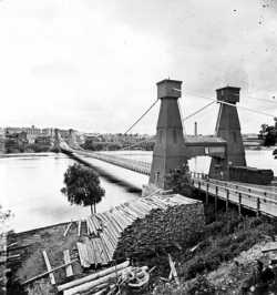 Black and white photograph of the Hennepin Bridge from Nicollet Island, c.1868.