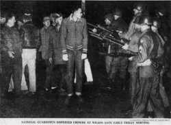 """Members of the National Guard confront striking meatpacking plant workers in Albert Lea. Printed in the Minneapolis Morning Tribune, December 12, 1959. Original caption: """"National Guardsmen dispersed crowds at Wilson Gate early Friday morning."""" Photograph by Charles Brill."""