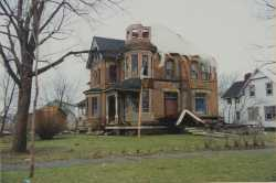 Photograph of badly damaged house.