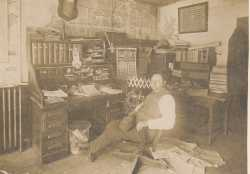Black and white photograph of Waconia Patriot editor and publisher Charles Reil in his office, 1917.