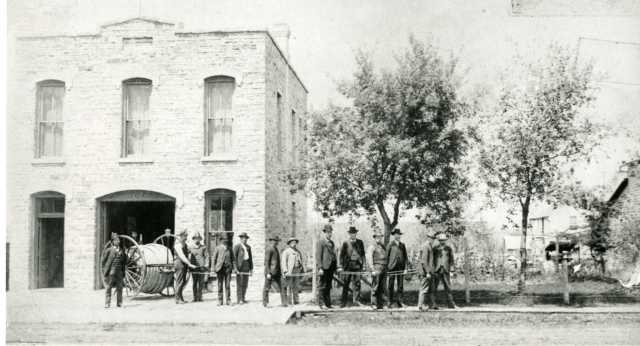 Black and white photograph of Cannon Falls firefighters posing in front of their headquarters.