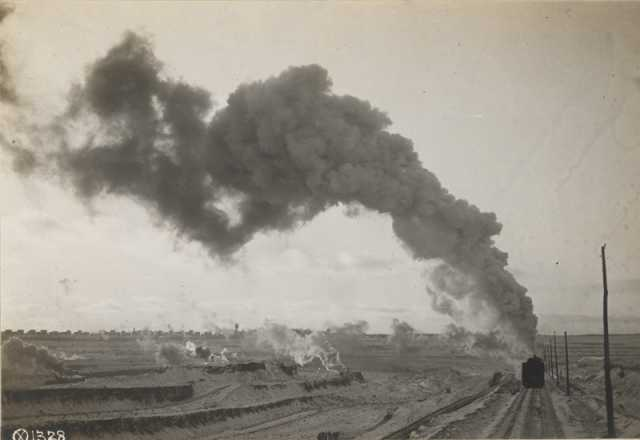 An Oliver Mining Company locomotive hauls ore away from an open pit near Hibbing, Minnesota, 1917. The young city is visible in the background.