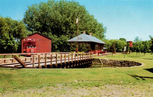 Postcard of the turntable, depot, engine house, and Grand Trunk Western caboose at End-o-Line Railroad Park and Museum, ca. 1980.