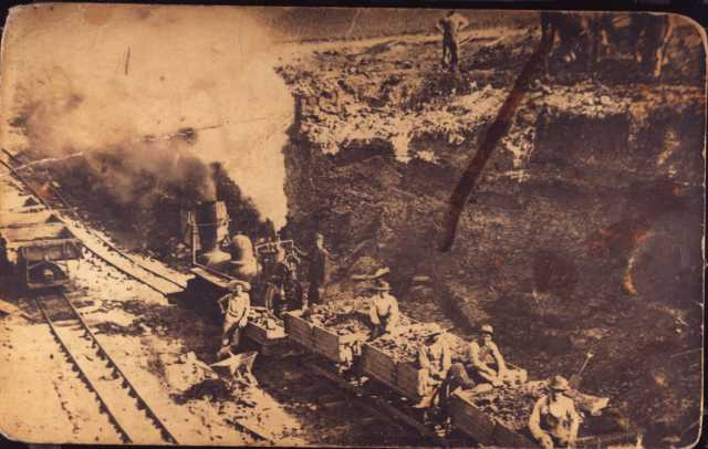 photograph of a train in a clay pit, filled with clay