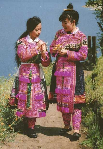 Color scan of a Hmong New Year postcard showing two young women in traditional Hmong dress, c.1980s.