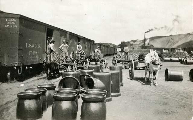 photograph showing clay sewer pipe sections next to a boxcar