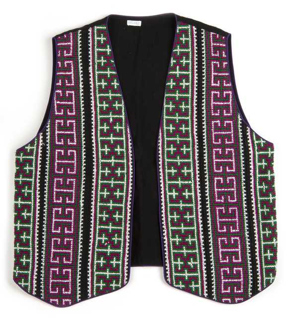 Color image of a reversible cotton vest with front panels of geometric cross-stitching made by a Minnesotan Hmong woman and sold by the Southeast Asian Ministry. Worn by Bea Vue-Benson, c.1999.