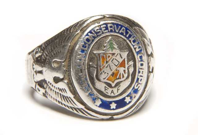 "Color image of a Sterling silver Civilian Conservation Corps ring with CCC logo flanked by an eagle and shield on opposing ends. Logo is engraved with ""3707/ and ""EAF"". Worn by Fred Fretheim of Company 3707, Two Harbors, MN, ca. 1936–1937."