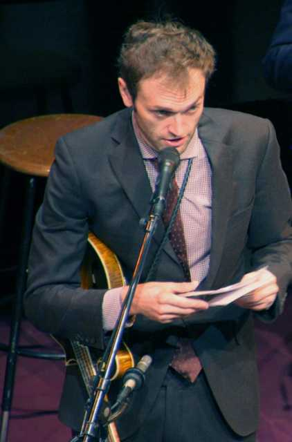 Prairie Home Companion host Chris Thile reads audience greetings during a broadcast at the Fitzgerald Theater in January 2016. Photograph by Wikimedia Commons user Jonathunder.