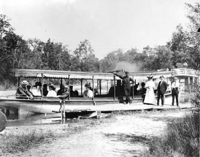 photograph of steamboat at a dock surrounded by passengers