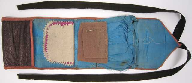 """A """"soldier's housewife"""" sewing kit made from a strip of leather with a twill-like finish and lined with silk."""