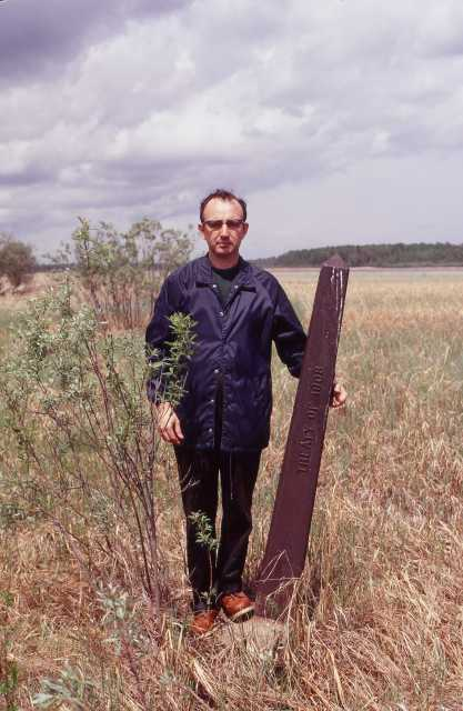 Color photograph of a Northwest angle marker and author William E. Lass provides a sense of the marker's scale, 1972.