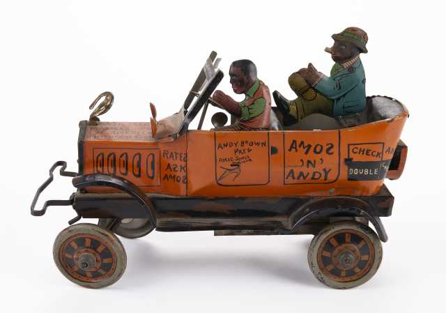 Metal windup toy car model of the Fresh Air Taxicab from the radio show Amos 'n Andy, made by Louis Marx and Co. of New York. It features two caricatured men riding in the car, the driver is wearing an orange vest, while the passenger wears a blue jacket and smokes a cigar. Made sometime between 1930 and 1939.