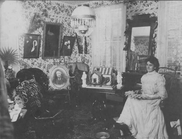 Black and white photograph of Susie Schmitt Hanson is seated wearing a light-colored long-sleeve floor-length dress.
