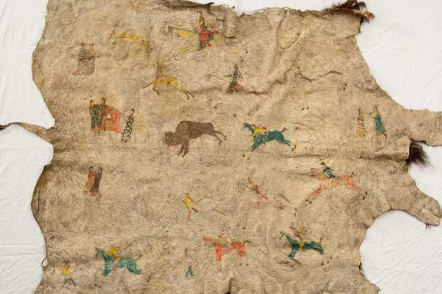 Buffalo robe painted with human figures, horses, and buffalo. Made by Dakota during the late nineteenth century.