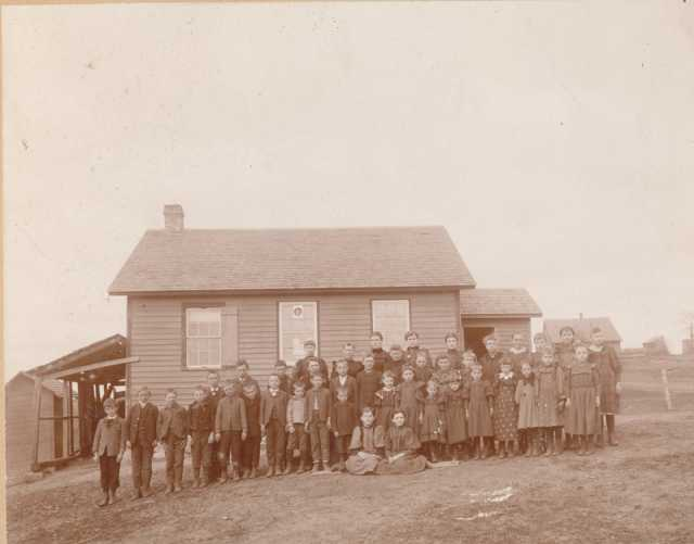 Photograph of Zoar public school (District #20) c.1895. Teacher Vena Abbott stands with her students outside the school building. Photograph Collection, Carver County Historical Society, Waconia.