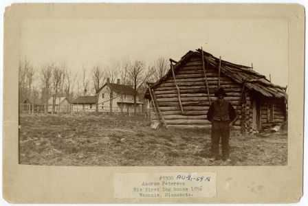 photograph shows Peterson in front of log house, with newer house in background