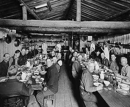 Black and white photograph of Lumberjacks eating in lumber camp dining hall, ca. 1916.