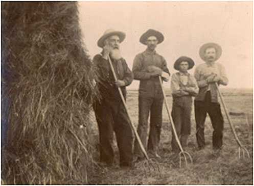 Black and white photograph of Father Anatole Oster (left) with farmers in Clontarf Township, c.1885.