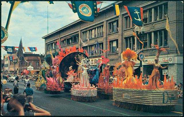 Parade floats passing down a Minneapolis Street for Aquatennial's Grande Day Parade, 1960.