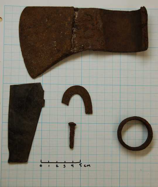 Color image of artifacts metal detected by a relic collector prior to 1972 and identified as an iron ferule, a piece of fire steel, a rosehead nail, a fragment from the bottom of a kettle, and an axe head.
