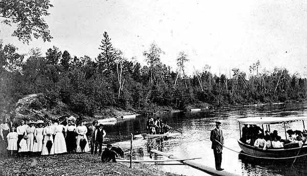 Photograph of a gathering of people on the banks of the upper Mississippi River for a prayer meeting conducted by Reverend John Sornberger c.1910.