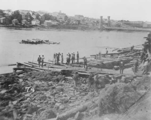 Black and white photograph taken just after the St. Anthony Falls Tunnel collapse, 1869. The Hennepin Suspension Bridge is visible in the background.