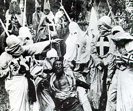 A scene from the movie Birth of a Nation (1915) featuring hooded Ku Klux Klan members surrounding Gus, a Black man portrayed in blackface by actor Walter Long.