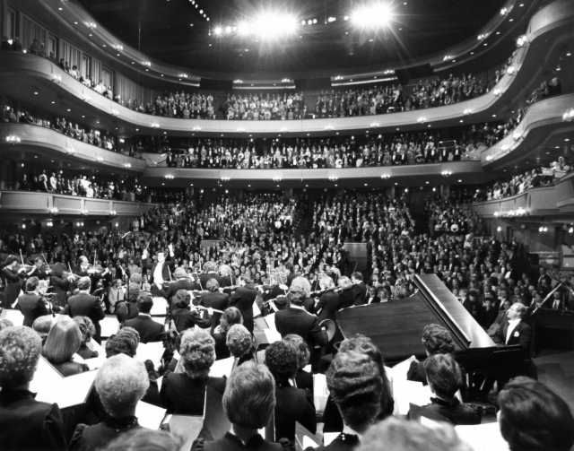 """Black and white photograph of the SPCO playing """"The Star Spangled Banner"""" at its Ordway debut concert, 1985."""