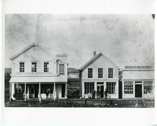 Black and white photograph of Van Campen store and Scofield's drug store, 1883.
