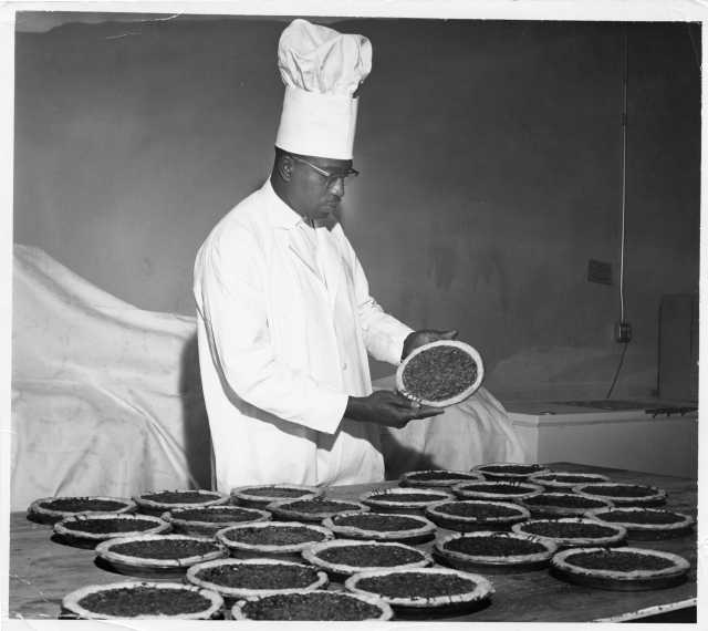 """Oscar C. Howard with pecan pies, ca. 1950s. From """"Cafeteria and Industrial Catering Business"""" in the Oscar C. Howard papers (P1842), Manuscripts Collection, Minnesota Historical Society."""