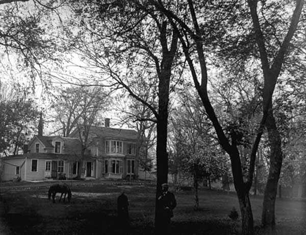 Black and white photograph of Harrington-Merrill house with Harry Merrill standing in the foreground, 1890.