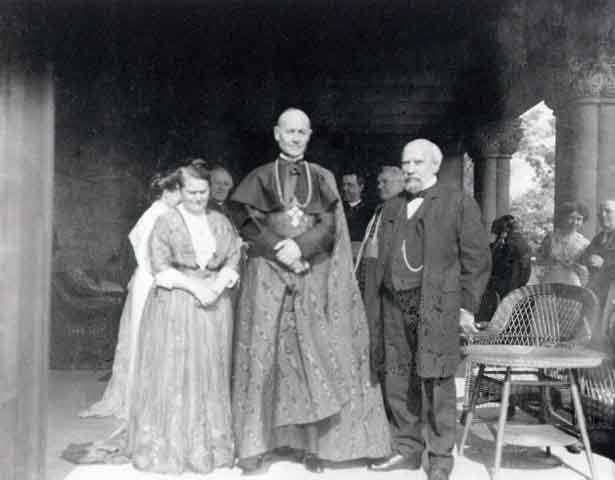 Black and white photograph of Mary T. and James J. Hill with Cardinal Vannutelli, a Papal delegate, on the Hill House veranda, 1910.
