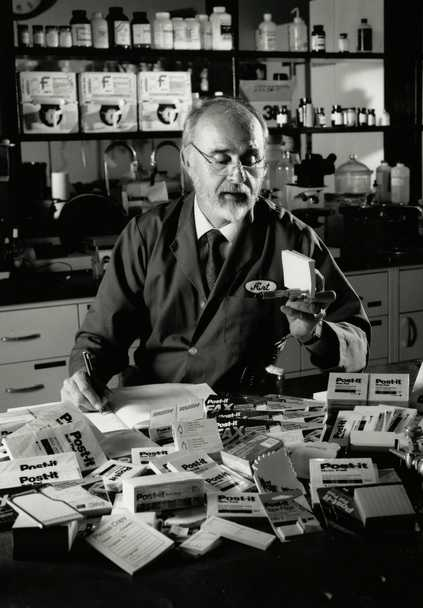 Black and white photograph of Arthur Fry inspecting his product, the Post-it Note, ca. 1980.