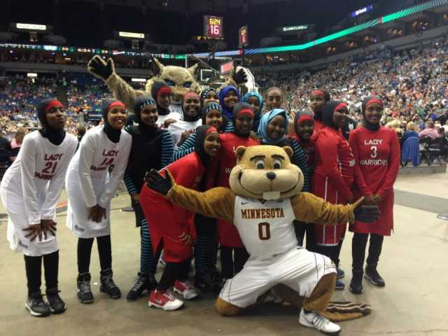The Lady Warriors (a basketball team representing Cedar-Riverside, a neighborhood in Minneapolis) pose with the University of Minnesota mascot Goldy Gopher and Minnesota Lynx mascot Prowl during project recognition at a Minnesota Lynx WNBA game, August 30, 2015.
