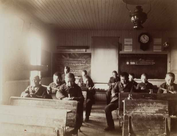 Black and white photograph of students inside a classroom at a Native American boarding school, c.1900.