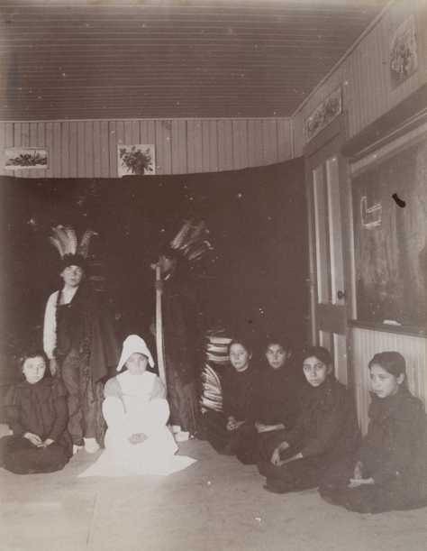 Black and white photograph of students at a Native American boarding school perform a Thanksgiving play, c.1900.