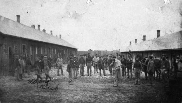Black and white photograph of some members of the First Minnesota Mounted Rangers in front of temporary barracks outside the walls of Fort Snelling, 1864.