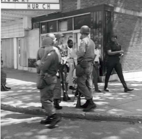 Black and white photograph of National Guardsmen patrolling Plymouth Avenue in North Minneapolis, July 1967.