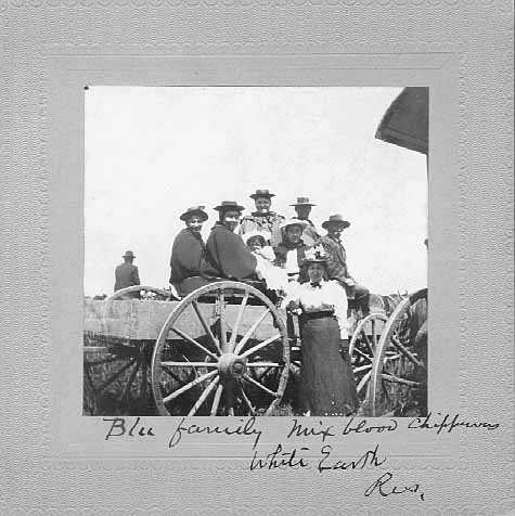 Black and white photograph of an eight-person mixed-blood Ojibwe family, including a baby, on the White Earth Reservation, ca. 1897.