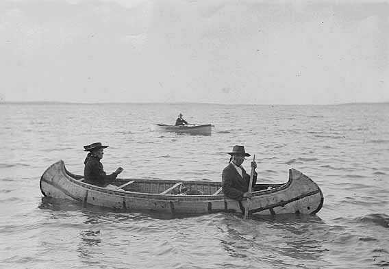 Black-and-white photograph of an Ojibwe birch bark canoe and two paddlers c.1910.